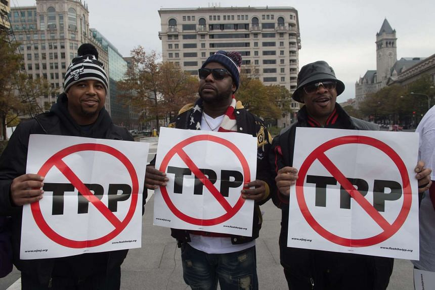 Men holding signs as they demonstrate against the Trans-Pacific Partnership (TPP) trade agreement in Washington, DC.