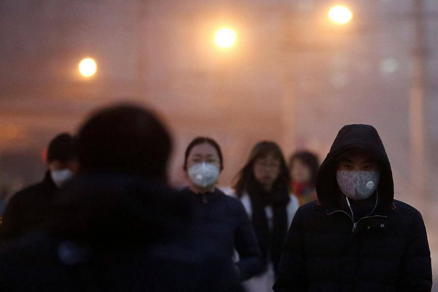 People wearing face masks as they cross a street on a polluted day in Beijing, China, on Jan 4, 2017.