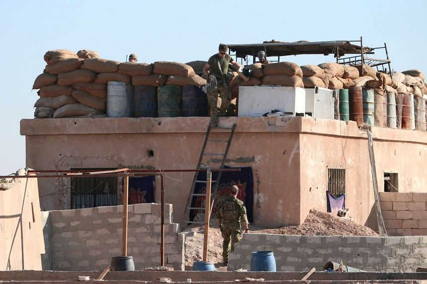 A US fighter walks down a ladder from a barricade, north of Raqqa city, Syria on Nov 6, 2016.