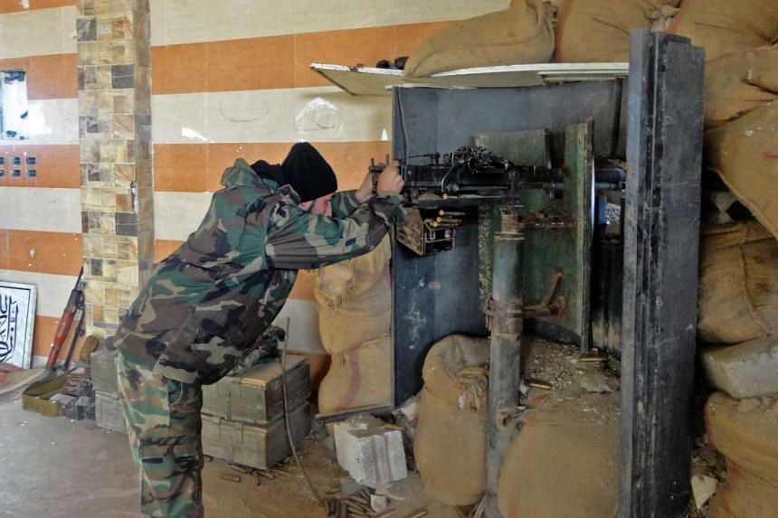 A Syrian army soldier takes aim in the government sector of the town of Houwayqa, which is besieged by Islamic State (IS) group jihadists, in the northeastern Syrian city of Deir Ezzor on November 12, 2016.