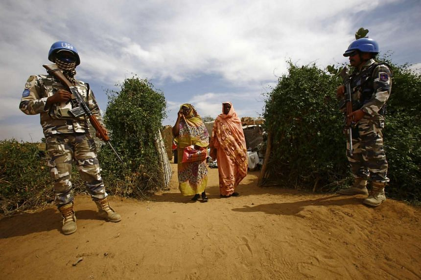 Women walk past UN peacekeepers standing guard at the Attash refugee camp in Nyala in South Darfur on Jan 9, 2017.