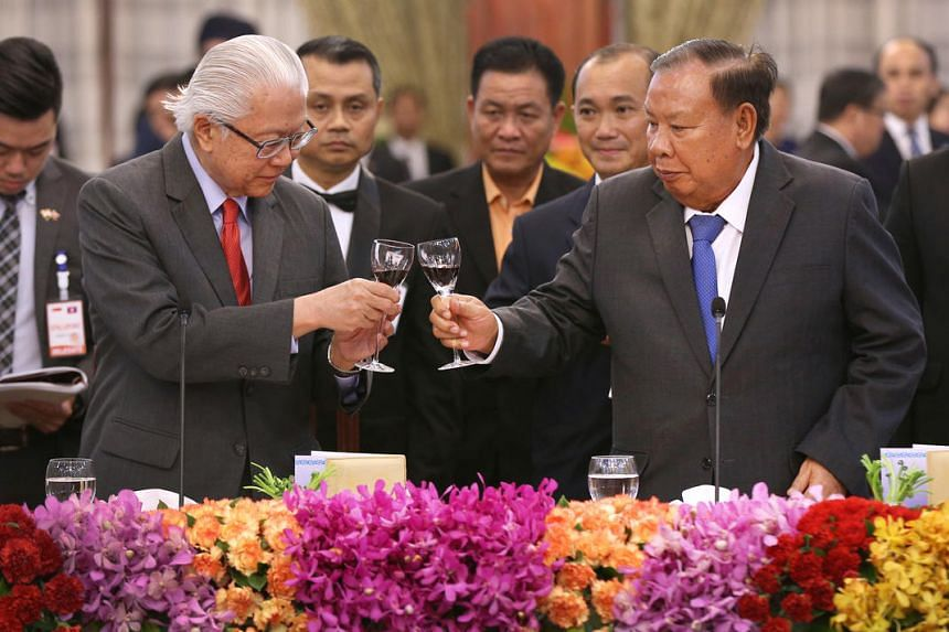 President Tony Tan Keng Yam (left) and Lao President Bounnhang Vorachit share a toast during the state banquet at the presidential palace in Vientiane, Laos, on Jan 12, 2017.