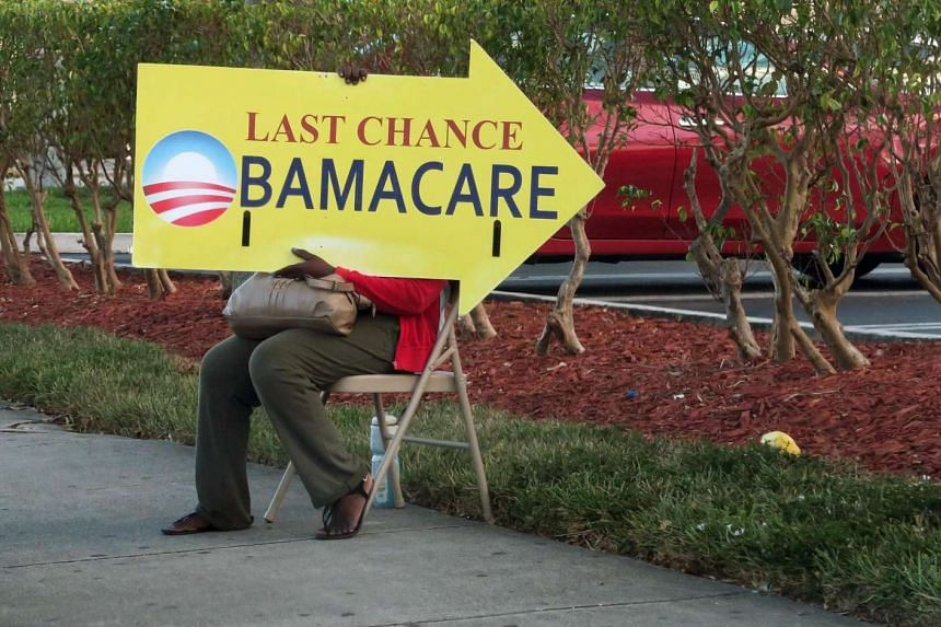 This file photo taken on Nov 27, 2016 shows a woman holding an Obama Care sign in front of a medical center in Miami.