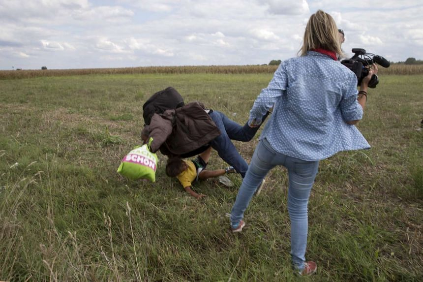 A migrant carrying a child falls after being tripped over by TV camerawoman Petra Laszlo while trying to escape from a collection point in Roszke village, Hungary on Sept 8, 2015.