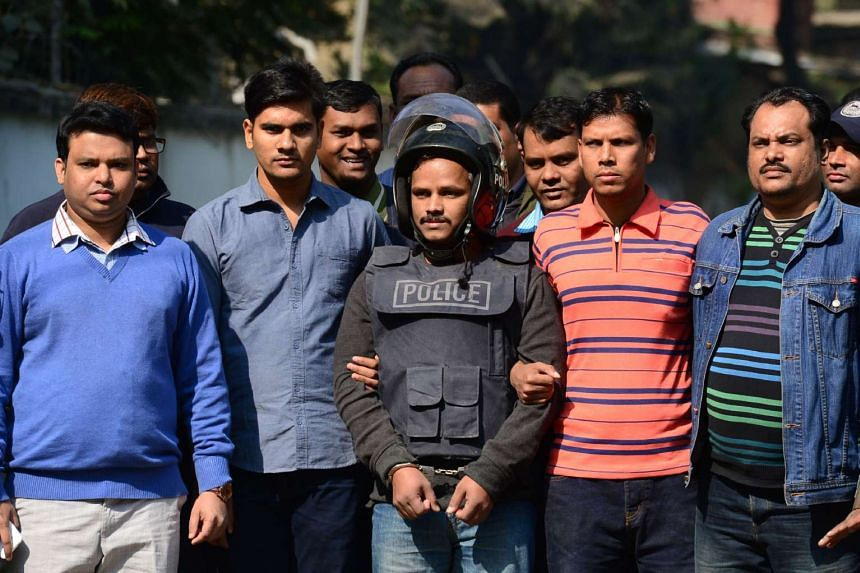Bangladesh police escort alleged Islamist militant Jahangir Alam (centre) in Dhaka on January 14, 2017, after his arrest in connection with an attack on the Holey Artisan Bakery attack last year.