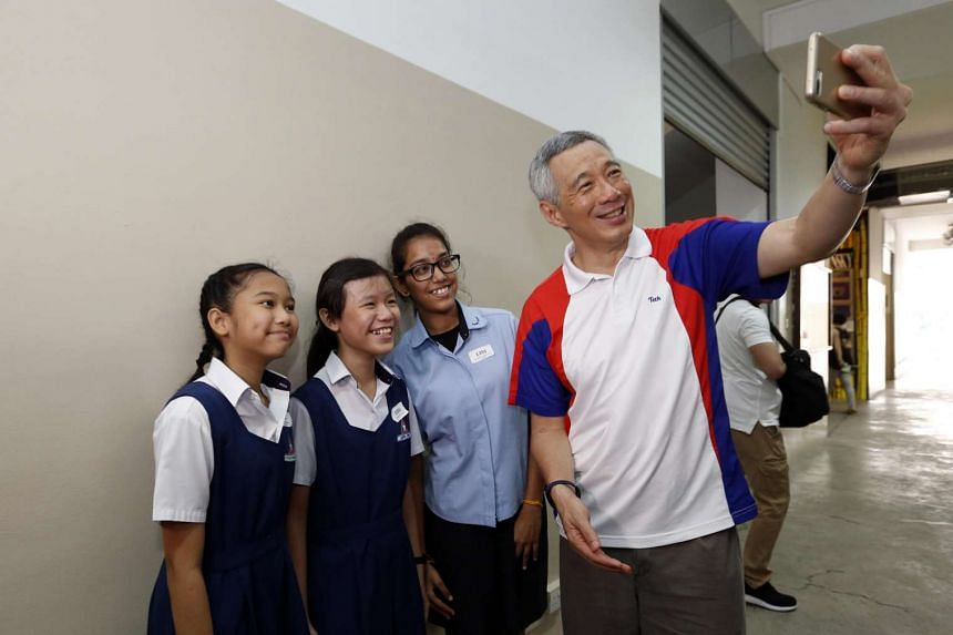 Prime Minister Lee Hsien Loong taking a wefie with Townsville Primary School students (from left) Dyan Nurqalisya Nurazhar, Janece Yong and Maheswari Selva Kumar.