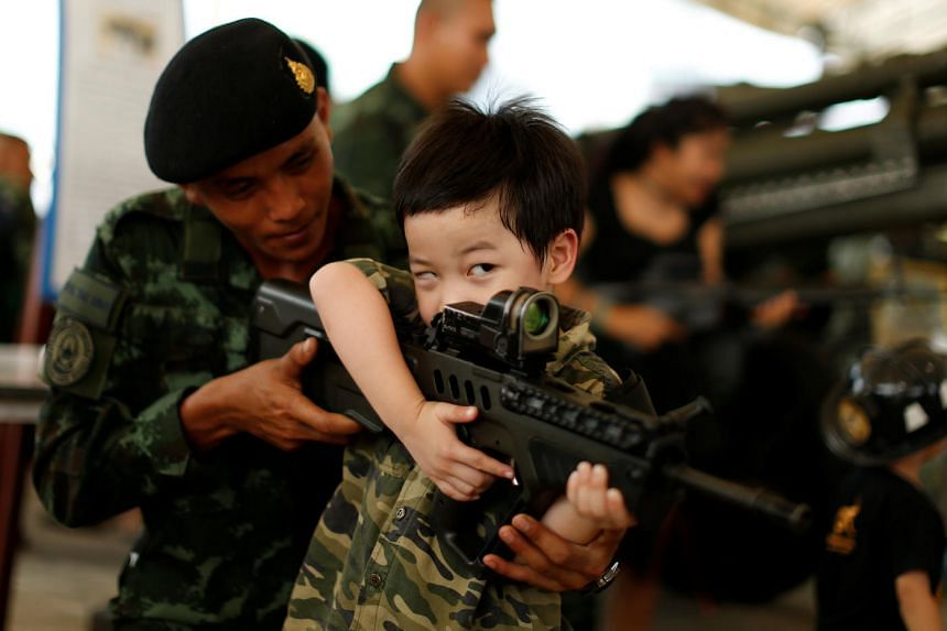 A Thai army soldier posing for a picture with a boy during a Children's Day celebration at a military facility in Bangkok, Thailand, on Jan 14, 2017.
