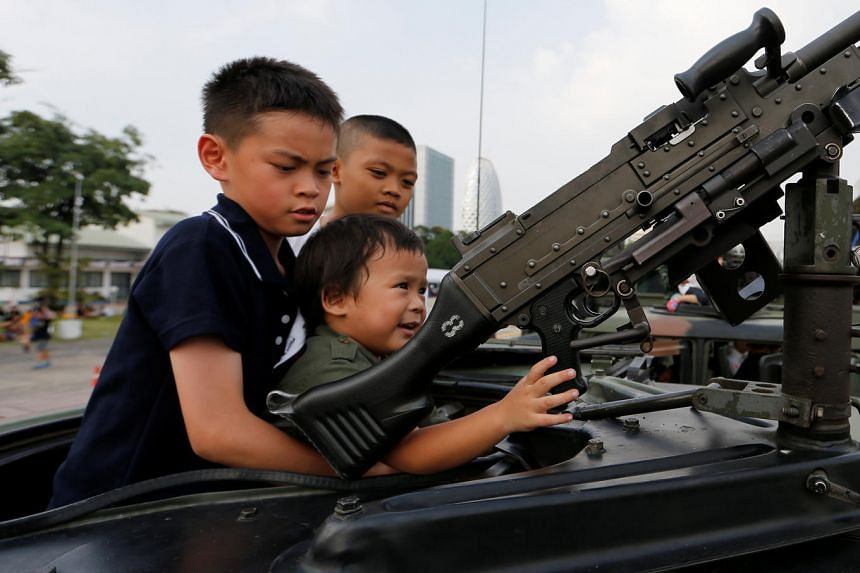 Children play with a weapon on top of an army vehicle during a Children's Day celebration at a military facility in Bangkok on Jan 14, 2017.