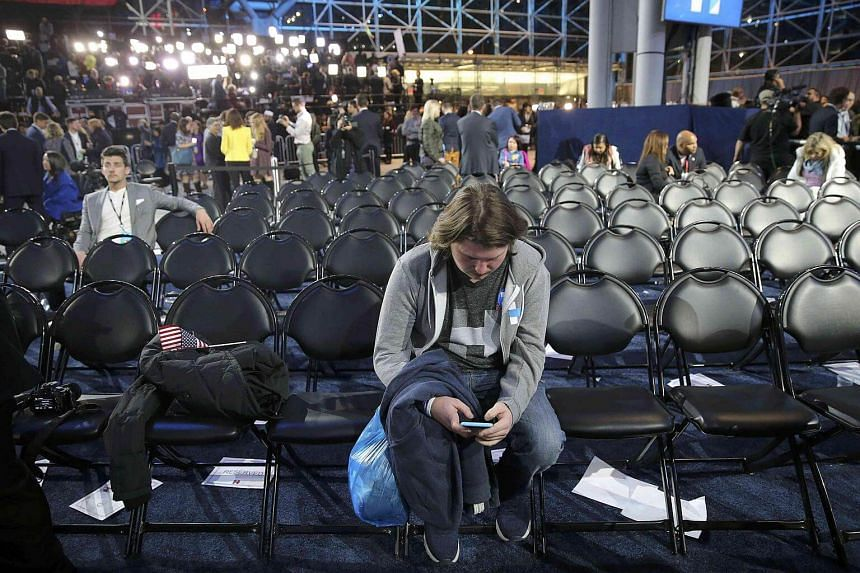 A supporter uses his smartphone as others leave Democratic US presidential nominee Hillary Clinton's election night rally in New York, US, on Nov 9, 2016.