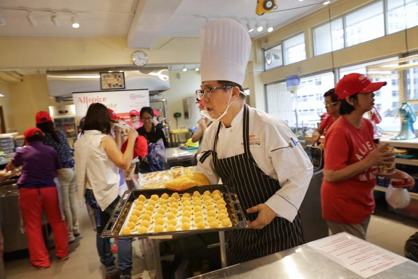 Chef Harry Ong, 67, taking the tray of pineapple tarts to the oven for baking.