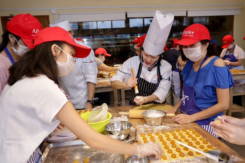 Chef Susan Tan, 60, showing participants (from left) Nicole Koo (in pink), 15, Shaniah Kiew, 15, and Shawna Goh, 45, how to brush the egg wash onto the dough.