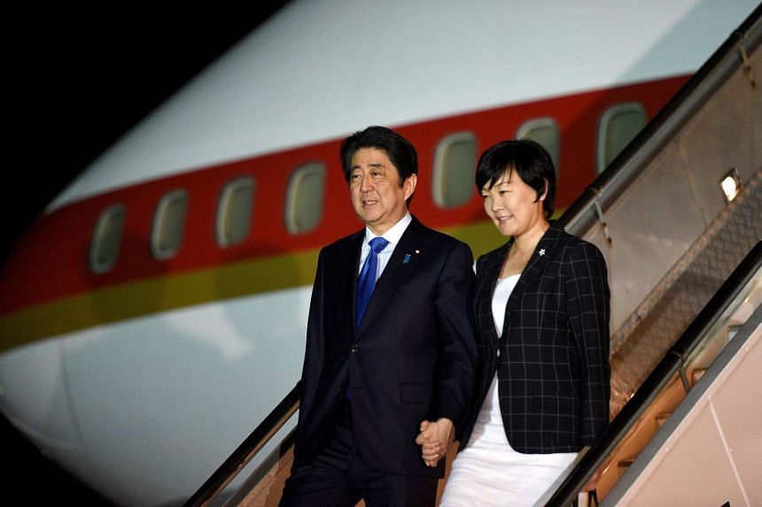 Japan's Prime Minister Shinzo Abe and his wife Akie disembark from their plane at the Sydney International airport, on Jan 13, 2017.