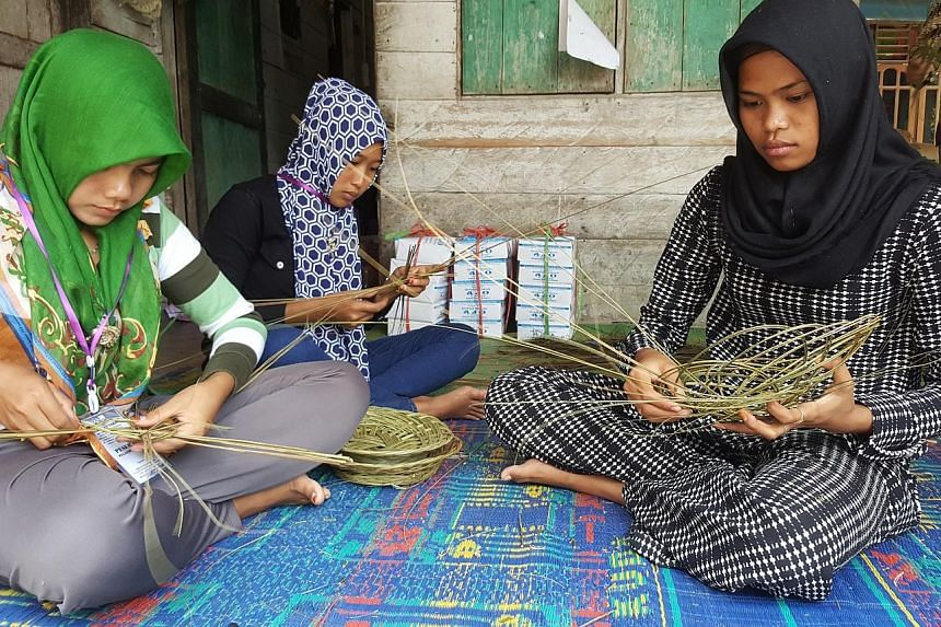 """Women from the village using stalks from the oil palm leaves to weave baskets. As part of the """"no-burn"""" method, farmers are taught to turn vegetative debris and wood waste into fertiliser for their crops. Thicker pieces of wood are sold to furniture-"""