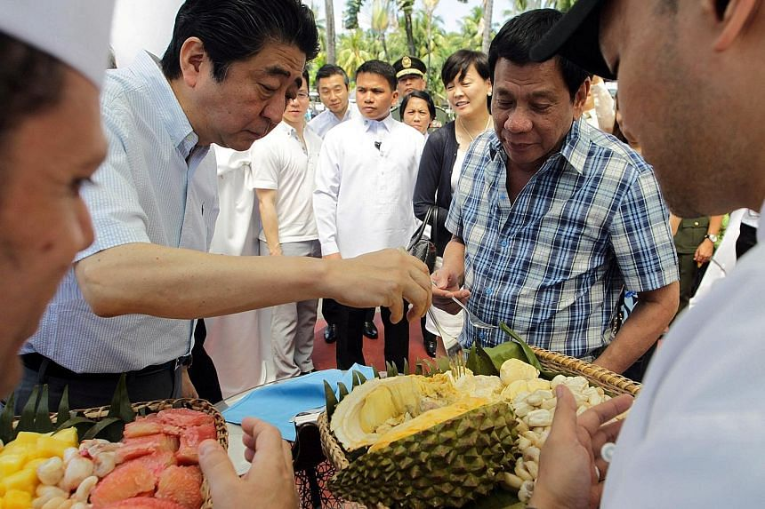 President Rodrigo Duterte giving Japan's Prime Minister Shinzo Abe (left) a tasting of durian, a key export of Davao, yesterday. Mr Abe has sought to woo the Philippines with a US$9 billion (S$12.8 billion) aid package, and has offered to help Mr Dut