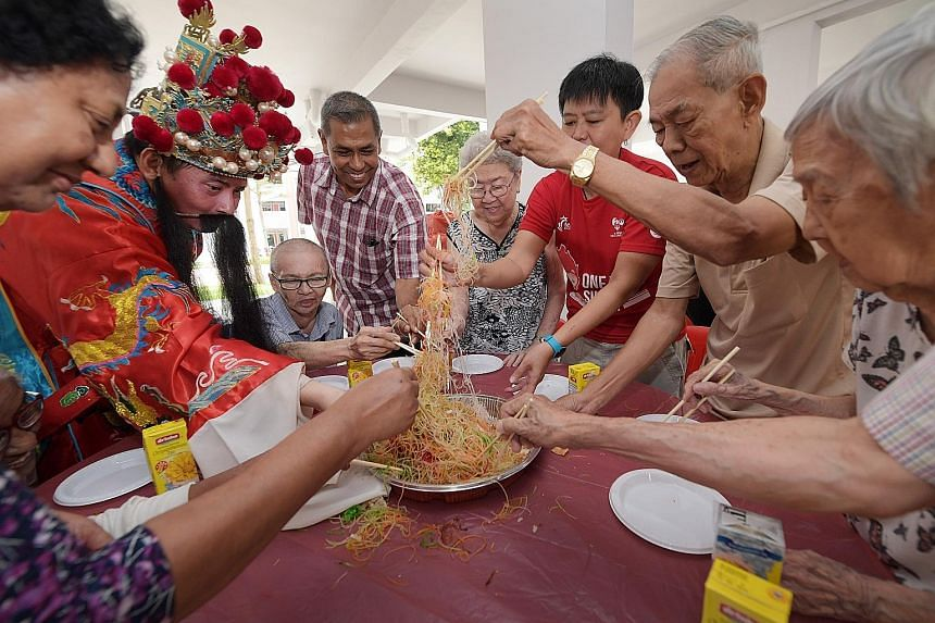 "Singapore Press Holdings (SPH) staff, one dressed as the God of Fortune, ""lo hei"" (tossing yusheng) with seniors from the AWWA Senior Community Home. SPH brought early Chinese New Year cheer to 120 residents yesterday, with more than 20 staff volunte"