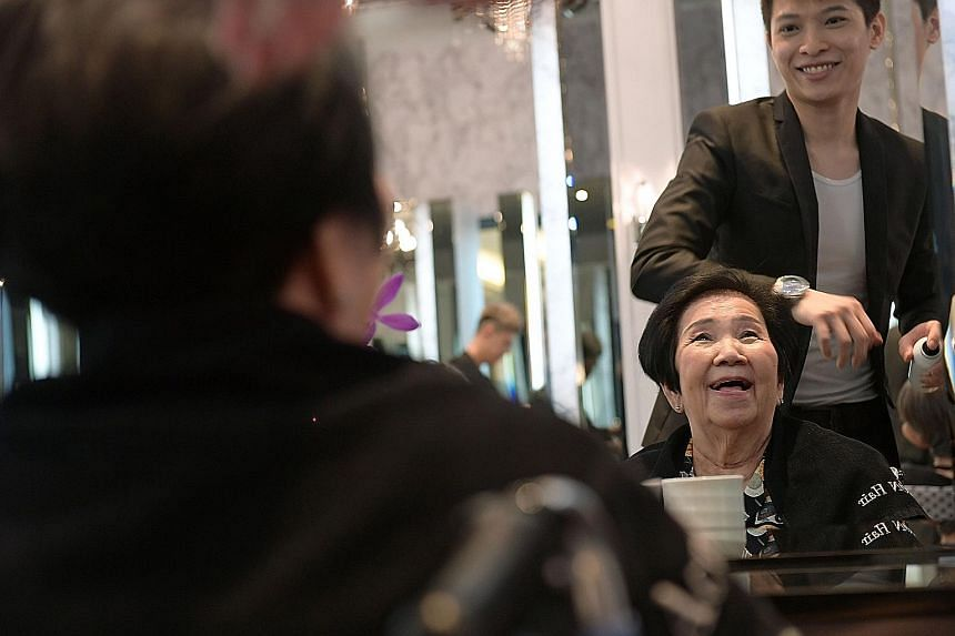 Ahead of Chinese New Year on Jan 28, Madam Ng Sook Cheng, 82, enjoyed a free hairstyling session yesterday, courtesy of Action Hair Salon - one of three Paragon mall tenants bringing festive cheer to elderly patients from the Home Nursing Foundation.