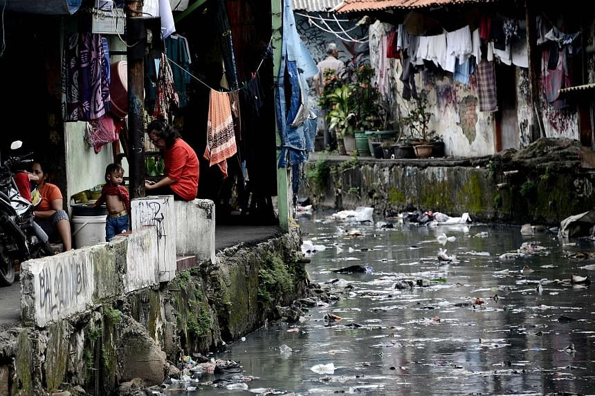 Workers cooling off in one of the tributaries of the Ciliwung River in the Indonesian capital Jakarta last month. Jakarta residents living along a narrow duct that typically runs through slums.