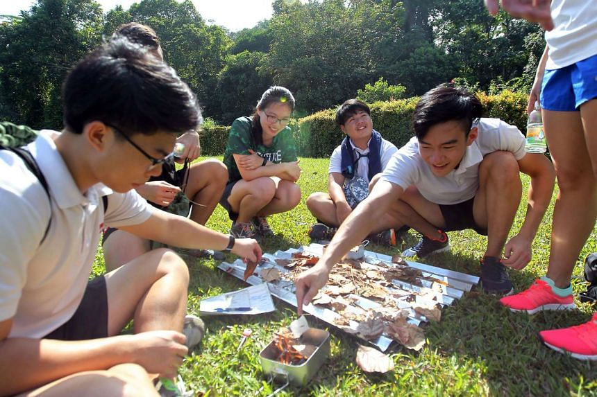 Students from ITE College working together to start a fire with a flint.