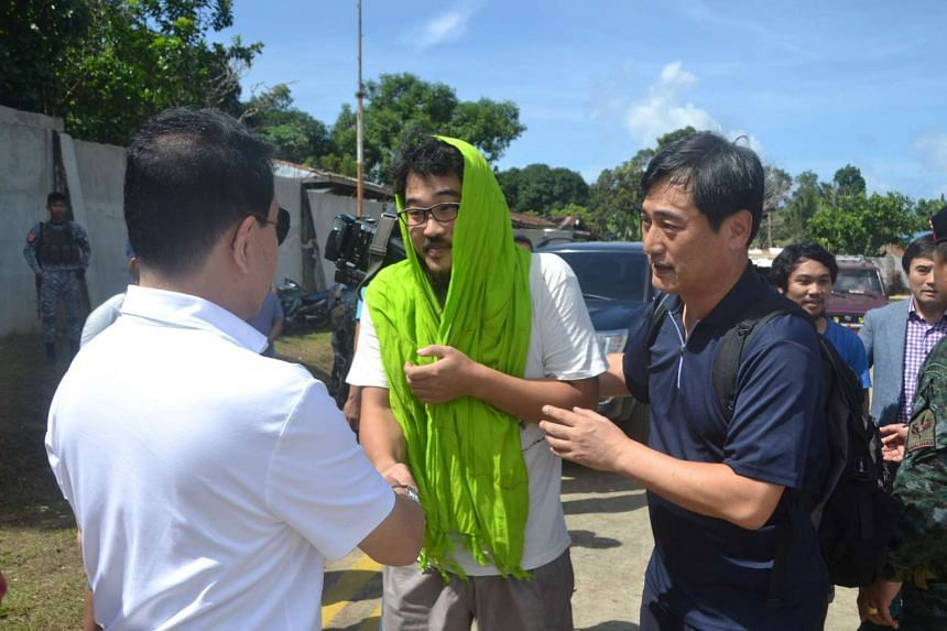 Park Chul Hong (centre), skipper of the South Korea-registered carrier DongBang Giant 2, is greeted by former Sulu governor Abdusakur Tan at Jolo airport in Sulu, southern Philippines on Jan 14, 2017.