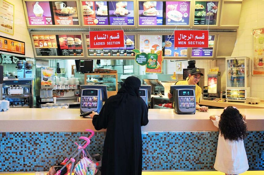 A woman and a girl buying food from a McDonald's outlet at the Mall of Dhahran in Dhahran, Saudi Arabia.