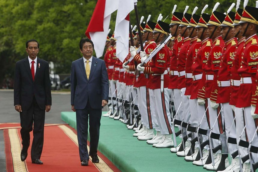 Japanese Prime Minister Shinzo Abe (centre), accompanied by Indonesian President Joko Widodo, inspects the honour guard during the arrival ceremony held at the Presidential Palace in Bogor, Indonesia on Jan 15, 2017.