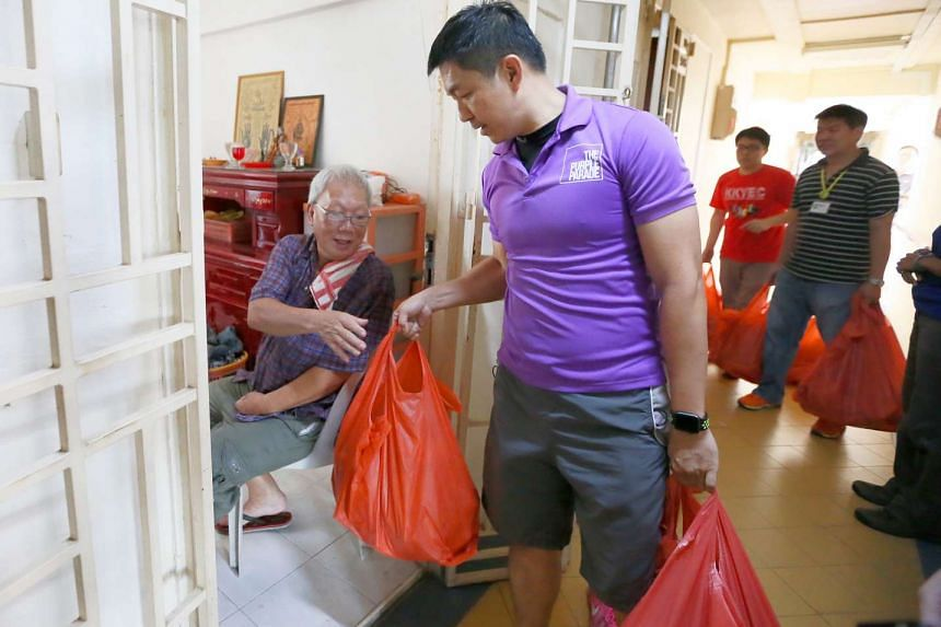 Minister Tan Chuan-Jin distributes food to Mr. Poh Kim Kah at Block 22 Chai Chee Road on Jan 15, 2017.