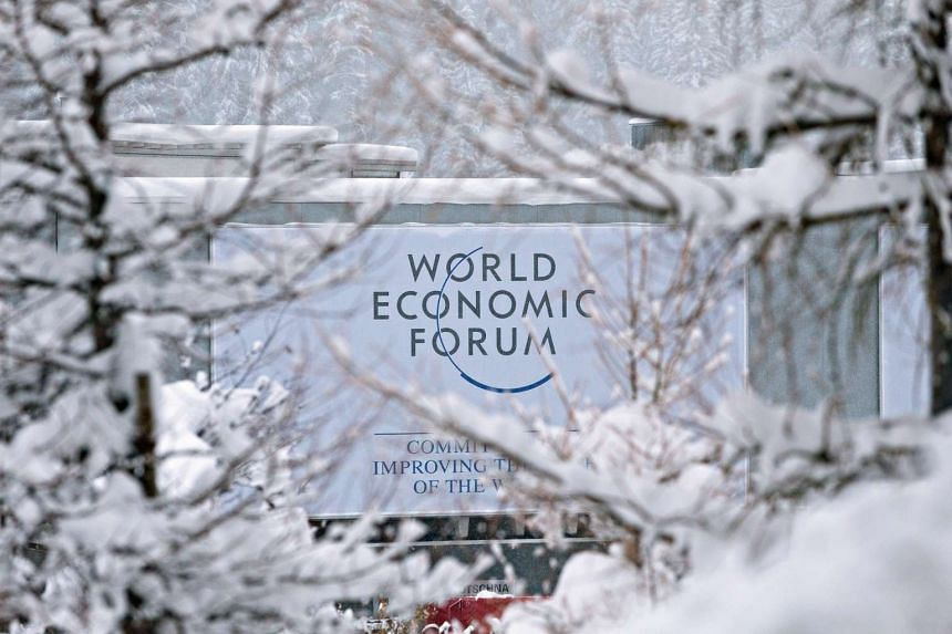 A sign for the World Economic Forum annual meeting sits on display among snow covered trees in Davos, Switzerland on Jan 14, 2017.