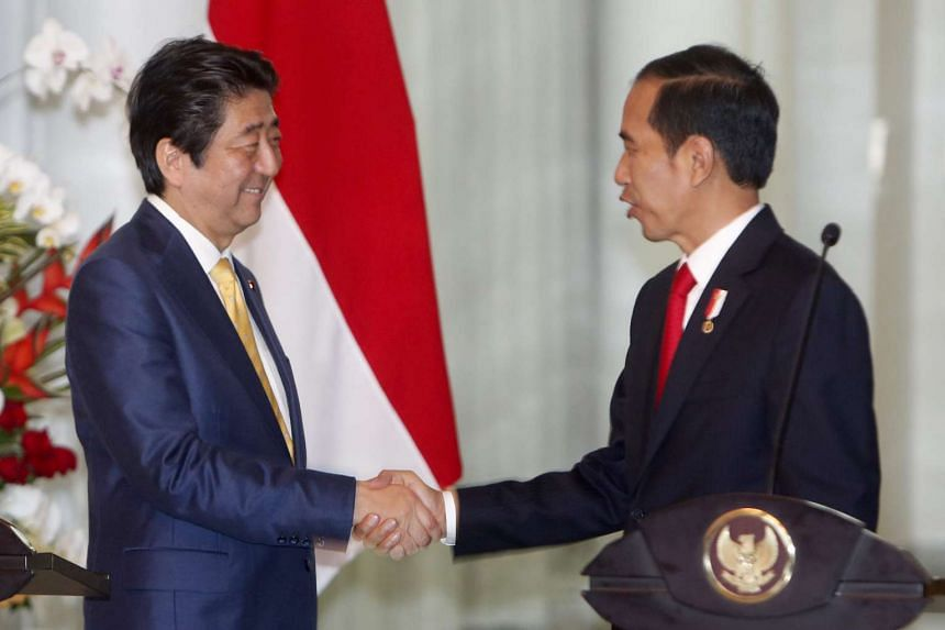 Japanese Prime Minister Shinzo Abe (left) and Indonesian President Joko Widodo (right) shake hands after a joint press conference at Presidential Palace in Bogor, Indonesia on Jan 15, 2017.