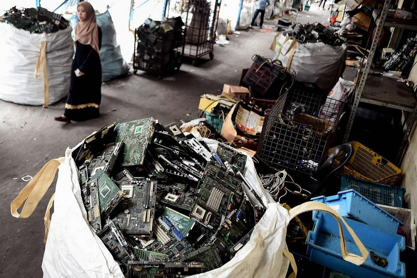 A woman walking past stacks of electronic waste at a Malaysian electronics recycling company in Shah Alam on Jan 13, 2017.