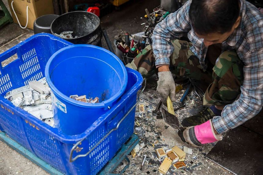 A worker taking apart electronic components at a recycling shop in Hong Kong on Jan 14, 2017.