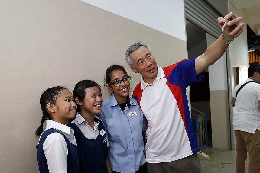 PM Lee taking a wefie with (from left) Primary 6 pupil Dyan Nurqalisya Nurazhar, Primary 5 pupil Janece Yong and Uma Maheswari Selva Kumar, who is entering Nanyang Polytechnic. All three received Edusave awards yesterday.
