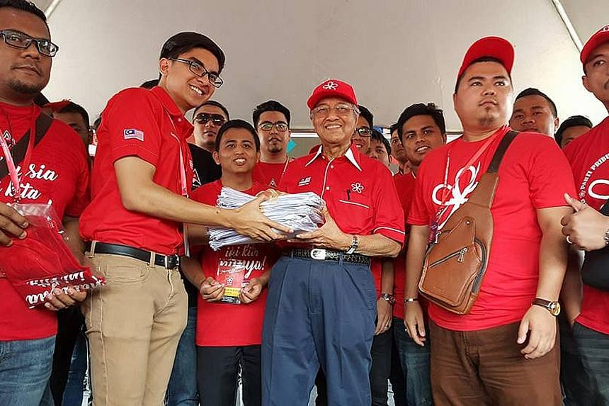 Dr Mahathir receiving application forms for membership in Parti Pribumi Bersatu Malaysia from the party's youth wing chief Syed Saddiq Syed Abdul Rahman at Shah Alam stadium yesterday.
