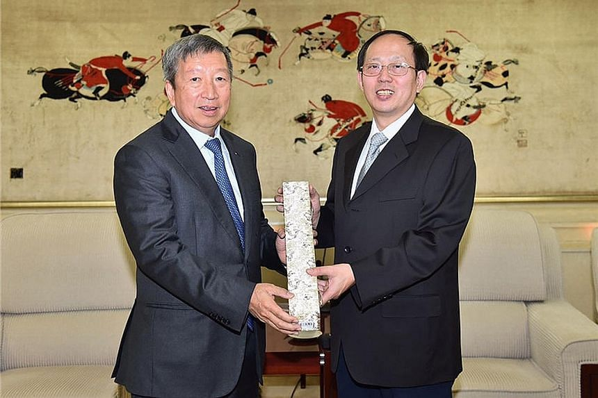 Singapore's International Olympic Committee executive board member Ng Ser Miang (left) receiving a souvenir gift from Gou Zhongwen, the newly elected president of the Chinese Olympic Committee during their meeting in Beijing on Wednesday. Gou, who is