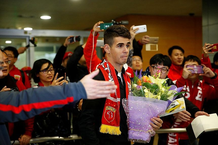A throng of fans welcoming Brazil midfielder Oscar at Shanghai Pudong International Airport. He is set to earn around £400,000 a week with Shanghai SIPG after joining from Chelsea.
