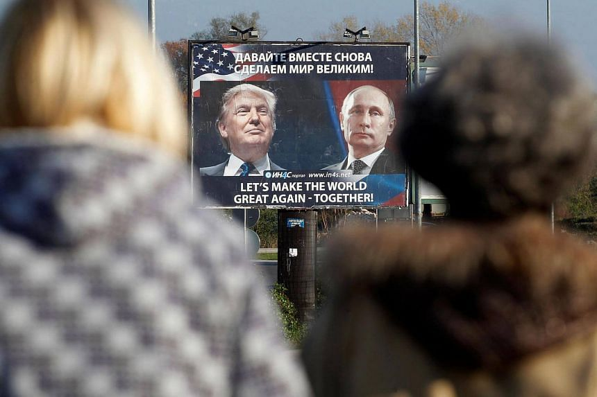 A billboard showing a pictures of US president-elect Donald Trump and Russian President Vladimir Putin is seen through pedestrians in Danilovgrad, Montenegro on Nov 16, 2016.