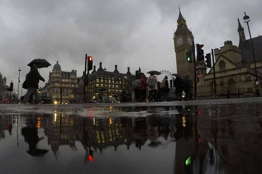 Pedestrians cross a street at Parliament Square during heavy rain in central London, Britain on Jan 12, 2017.