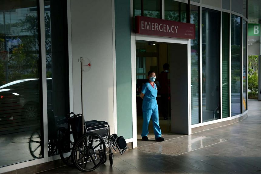 A member of the hospital staff waits at the entrance of the Accident and Emergency Department of Ng Teng Fong Hospital at Jurong East.