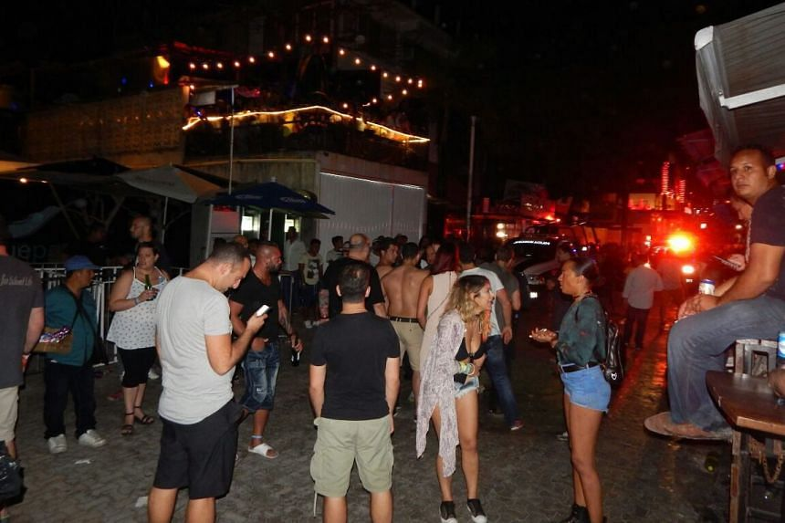 People wait outside a club where a shooting took place in Playa del Carmen, Mexico, early on Jan 16, 2017.