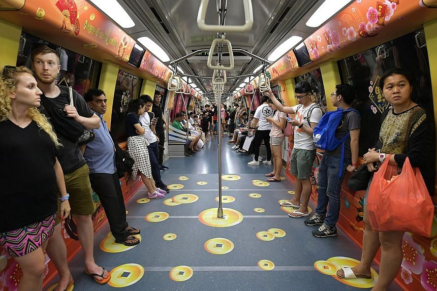 Commuters on the North-East Line may spot gold coins on the floor of a train cabin - but they aren't the real deal. To celebrate the coming Chinese New Year, the train has also been decorated with rooster, hen and chick motifs, along with traditional