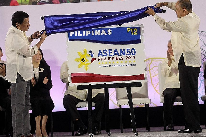 Philippine President Rodrigo Duterte (far left) and Postmaster General Joel Otarra unveiling the Asean Chairmanship Special Stamp at the SMX Convention Centre in Davao yesterday, as the country took over chairmanship of the regional grouping.