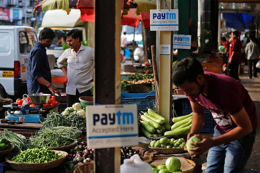 Roadside stalls in Mumbai displaying signs that they accept digital payments via Paytm, a digital-wallet company. Following his decision in November to demonetise high-value currency notes of 1,000 rupees and 500 rupees to curb corruption and illegal