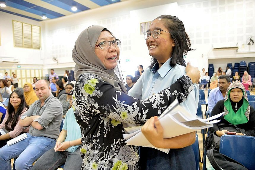 Hong Kah Secondary student Haziratul Zakirah Ghazali, one of her school's top scorers in the O-level exams, being congratulated by her mother, Madam Siti Rodiyah, last Wednesday. She aims to study medicine in university one day to fulfil her dream of