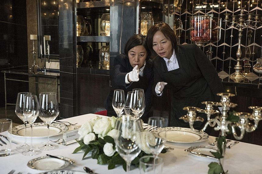 Ms Liu Janmin (left) and Ms Zhang Ling, who are studying to be butlers, checking the alignment of glasses on a table set for a formal dinner.