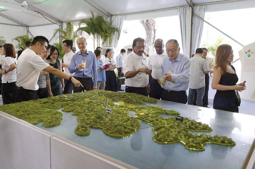 Visitors looking at a model of the new integrated nature and wildlife park at Mandai.
