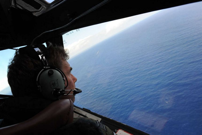 Crew members on board a Royal New Zealand Airforce P-3K2 Orion searching for traces of the missing MH370 off Perth on April 13, 2014.