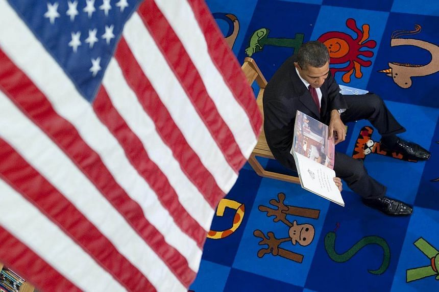 US President Barack Obama reading a book to students at Long Branch Elementary School in Arlington, Virginia.