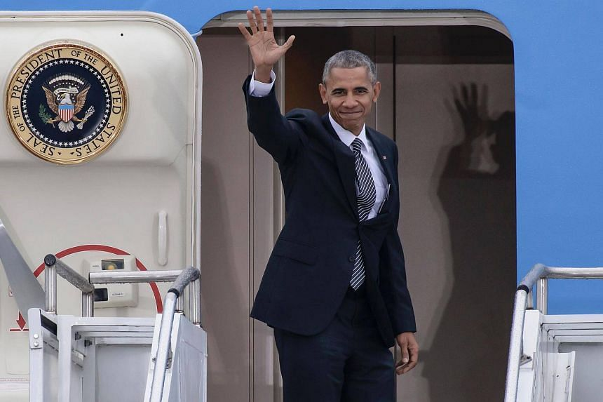 US President Barack Obama waving as he enters Air Force One prior to his departure from the Tegel airport in Berlin.