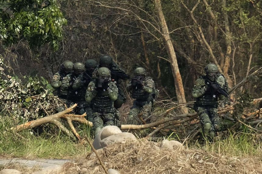Taiwan special forces personnel move in formation through vegetation during an annual military drill in Taichung on Jan 17, 2017.