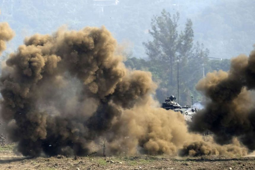 A US-made M60A3 tank is seen behind smoke charges during an annual military drill in Taichung on Jan 17, 2016.