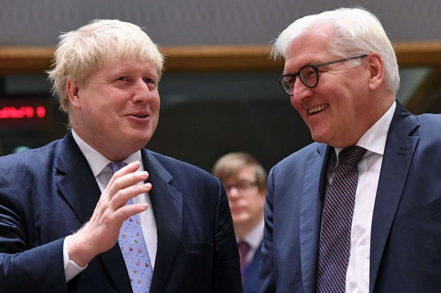 Germany's Foreign Minister Frank-Walter Steinmeier (right) and British Foreign Secretary Boris Johnson chat at the European Council in Brussels on Jan 16, 2017.